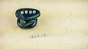 Das Konzept der Zeit SETZEN Sie Zeit Würfelbuchstaben auf dem schwarzen Stein fest, der Sandhintergrund schriftlich ist Stockfotografie