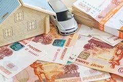 Das Konzept des kaufenden Eigentums und des Autos: der Plan des Hauses, die Schreibmaschine und ein Stapel russische Rubel im Ban Lizenzfreie Stockfotografie