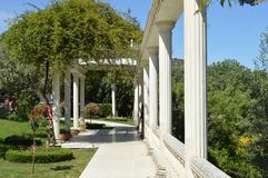 Das Konzept des Landschaftsdesigns im Garten, in einem schönen Gitter mit einer Spalte, in den Blumen und in den Bäumen stockbild