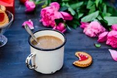 Das Konzept des Morgenkaffees in einer romantischen Art auf dem schwarzen hölzernen Hintergrund Pfingstrosenblumen und Blumenblät Lizenzfreie Stockfotos