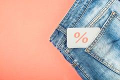 Das Konzept des Verkaufs, schwarzer Freitag, ein Rabatt mit Blue Jeans auf einem roten Hintergrund mit einem Tag in Ihrer Draufsi Stockbild