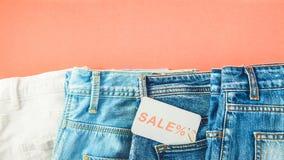 Das Konzept des Verkaufs, schwarzer Freitag, ein Rabatt mit Blue Jeans auf einem roten Hintergrund mit einem Tag in Ihrer Draufsi Lizenzfreie Stockfotos