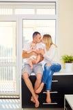 Das Konzept einer glücklichen Familie Vater, Mutter und Baby, die a sitzen lizenzfreies stockbild