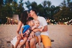 Das Konzept eines Familienurlaubs Junge Familie, die auf einer Bank am Abend auf einem sandigen Strand sitzt Mutter- und Vatikuß, Lizenzfreies Stockfoto
