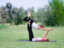 Das Konzept eines gesunden Lebensstils Zwei Frauen, die Yoga im Park tun stockbild