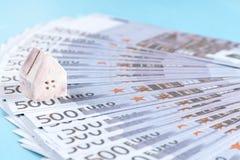 Das Konzept eines Spielzeughauses auf einem Hintergrund von Banknoten von 500 e Lizenzfreie Stockbilder