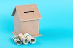 Das Konzept von den Sparguthaben, zum eines Hauses zu kaufen Geldkasten, Dollar in den Rollen, auf blauem Hintergrund Stockfotografie