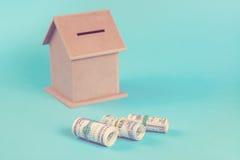 Das Konzept von den Sparguthaben, zum eines Hauses zu kaufen Geldkasten, Dollar in den Rollen, lokalisiert auf blauem Hintergrund Stockfotografie