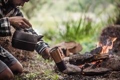 Das Konzept von kampieren der Kerl auf der Art des Feuers lizenzfreie stockbilder