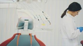 Das Konzept von Leuten, von Medizin, von Zahnheilkunde und von Gesundheitswesen Ein Zahnarzt der jungen Frau, der Handschuhe währ stock video