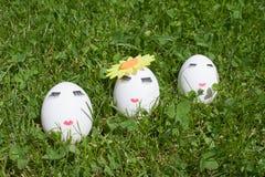 Das Konzept von Ostern, zum von drei Eiern zu malen, bilden auf grünem Gras Stockfotos