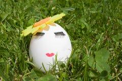 Das Konzept von Ostern, zum von einem Ei zu malen, bilden auf grünem Gras Lizenzfreie Stockfotos