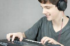 Das Kopfhörer-Tragen jugendlich justiert Tastatur Stockfoto