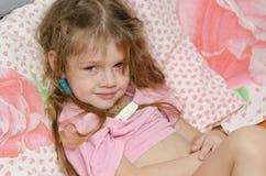 Das kranke Mädchen mit drei Jährigen misst die Temperatur Stockfoto