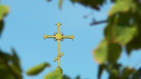 Das Kreuz auf der Haube unter Blättern stock footage