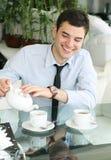 Das Lächeln jungen der Männer gießt Tee in ein Cup. Lizenzfreie Stockfotos