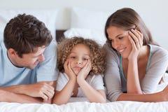 Das Lächeln parents das Lügen auf einem Bett mit ihrem Sohn Stockfotos