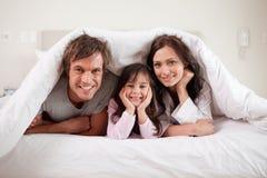 Das Lächeln parents das Lügen unter einem Duvet mit ihrer Tochter lizenzfreie stockbilder