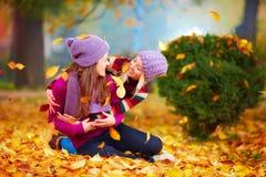 Das Lächeln von den Freunden, die Spaß zusammen im Herbstpark unter dem Fallen haben, verlässt Stockbild
