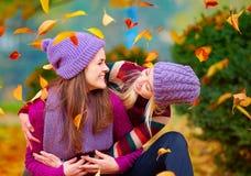 Das Lächeln von den Freunden, die Spaß zusammen im Herbstpark unter dem Fallen haben, verlässt Lizenzfreie Stockfotografie