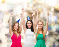 Das Lächeln von Frauen in der Partei bedeckt Daumen sich zeigen mit einer Kappe Stockbild