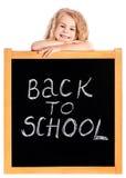 Das lächelnde blonde kleine Mädchen, das auf Schule sich lehnt, schwärzen Tafel Stockfoto