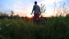 Das lächelnde glückliche Paar geht mit Fahrrädern entlang dem schönen blühenden Feld während des hellen bunten Sonnenuntergangs stock footage