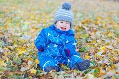 Das lächelnde lustige Baby, das auf Gelb sitzt, verlässt im Herbst Stockfotografie