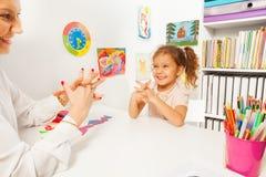 Das lächelnde Mädchen, das Finger tut, trainiert als ihr Lehrer Lizenzfreie Stockfotografie