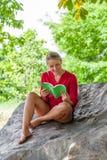 Das lächelnde Mädchen 20s, das einen Sommer liest, buchen unter einem Baum Lizenzfreie Stockfotos