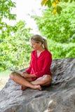 Das lächelnde Mädchen 20s, das einen Sommer liest, buchen unter einem Baum Stockfotografie