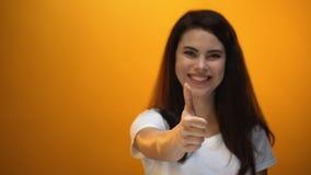 Das lächelnde Mädchen, das sich Daumen, erfüllter Kunde zeigt, mag Service, gutes Feedback stock footage