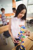 Das lächelnde Schulmädchen, welches das Molekül überprüft, modellieren im Labor Stockfotografie