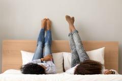 Das Lügenc$plaudern der afrikanischen Freundinnen auf Bett hob Beine oben an stockfotografie