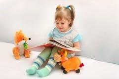 Das Lachen des kleinen Mädchens, das Abbildungen betrachtet. Stockfotografie