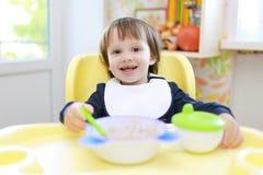 Das Lachen von 2 Jahren Kleinkind isst zu Abend Lizenzfreie Stockbilder