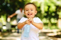 Das lachende Laufen des kleinen Jungen im Freien mit einer Flasche eines klaren Trinkwassers, sein Vater wird im Hintergrund verw stockbild