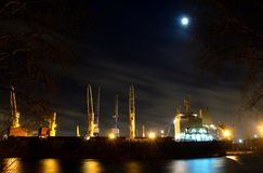 Das LadenFrachtschiff mit Kränen wird im Hafen nachts festgemacht Lizenzfreie Stockfotos