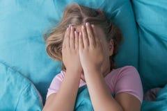 Das langhaarige blonde Lügen des Mädchens ziehen an sich auf blauen Bettbedeckungs-Fellgesichtshänden zurück Früh geweckt Frecher Lizenzfreies Stockbild