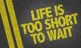 Das Leben ist zur Wartezeit zu kurz, die auf die Straße geschrieben wird Stockbilder