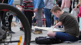 Das Leben von behindertem, Künstler mit den kranken Händen macht Kunst auf Straße unter Passanten stock footage
