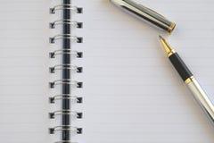 Das leere Notizbuch und ein silberner Stift Lizenzfreies Stockfoto