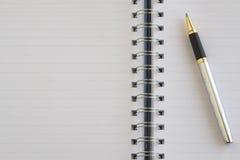 Das leere Notizbuch und ein silberner Stift Lizenzfreies Stockbild