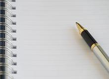 Das leere Notizbuch und ein silberner Stift Stockbild