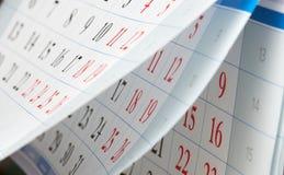 Das Leicht schlagen des Kalenders bedeckt mit den schwarzen und roten Zahlen Lizenzfreie Stockfotos