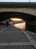 Das letzte Sonnenunterganglicht auf der Seine als Touristen gehen unter eine Brücke auf der linken Bank Lizenzfreie Stockfotos