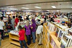 Das Leuteeinkaufen für Bücher auf den Millivolt-Zeichen hoffen Stockfotos