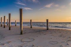Das Licht der goldenen Stunde am Strand mit hölzernen Stapel und Herzzeichnungen im Sand stockbild