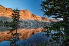 Das Licht des Sonnenaufgangs reflektiert ein Bild der Berge weg von der ruhigen Oberfläche von einem See stockfoto