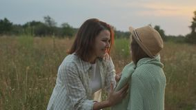 Das Lieben von Müttern setzt sich auf die Tochter gestrickte Decke und umarmt Kind stock footage